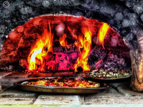 Pizzas in a clay oven
