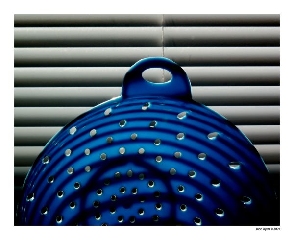 Photo of blue plastic strainer and window blinds
