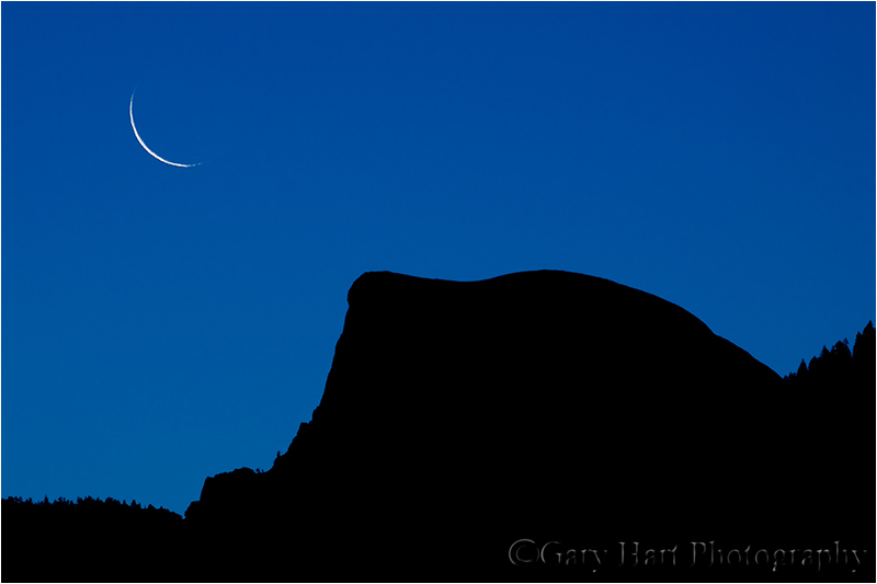 Crescent moon rises above Half Dome at sunrise