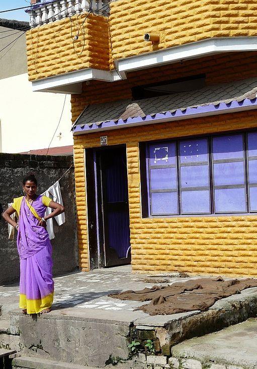 une dame devant sa petite maison
