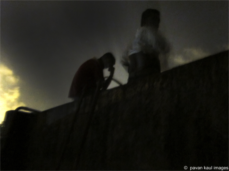 Men atop terrace water tank at night...?
