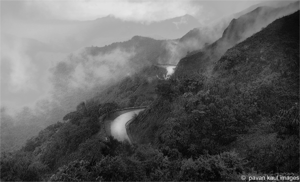 a road winding up hills and clouds