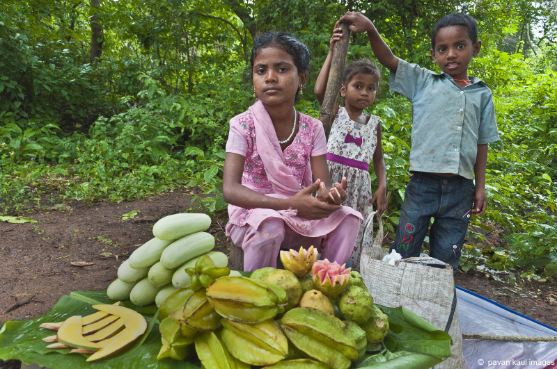 tribal children selling fruit by forest roadside