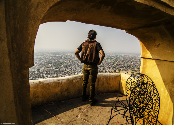 man looking out at city view from fortress balcony