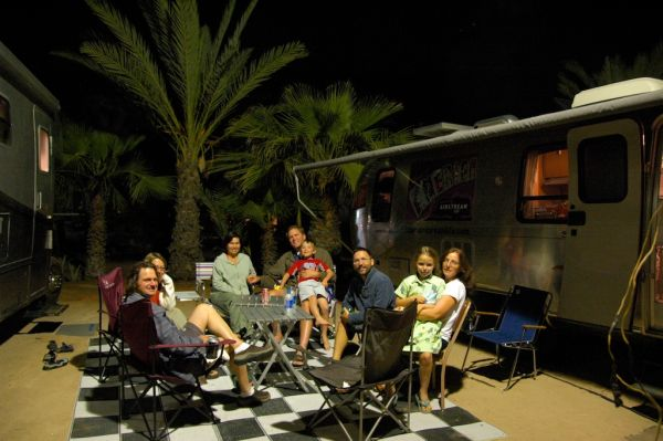 Family gathering at night by the Airstream
