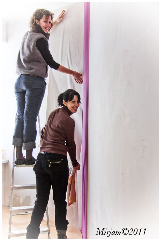 2 ladies setting up wallpaper