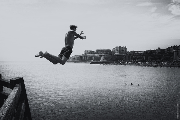 Young man jumping into the sea at Broadstairs