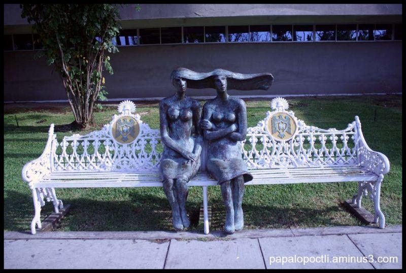 Dos figuras femeninas sentads en una banca
