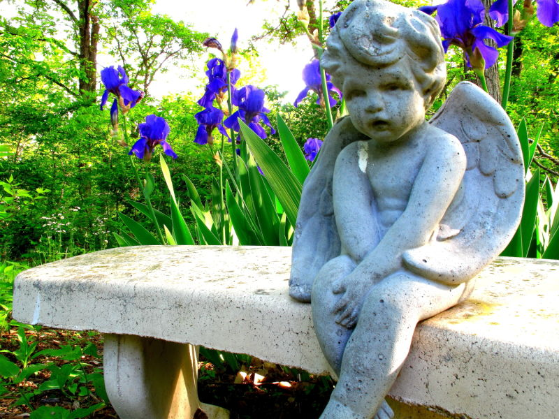 an angel sitting on a bench with flowers