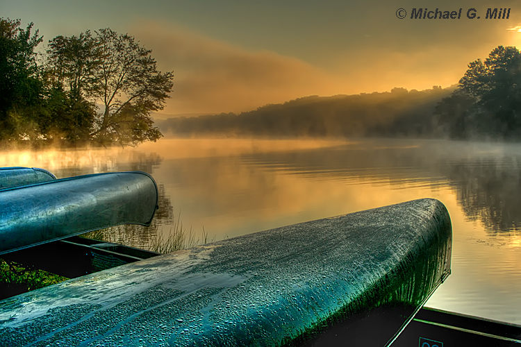 Canoes moored by a lake with early morning mist