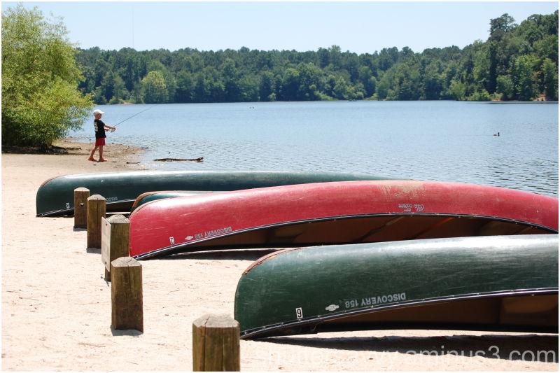 boy fishing near canoes