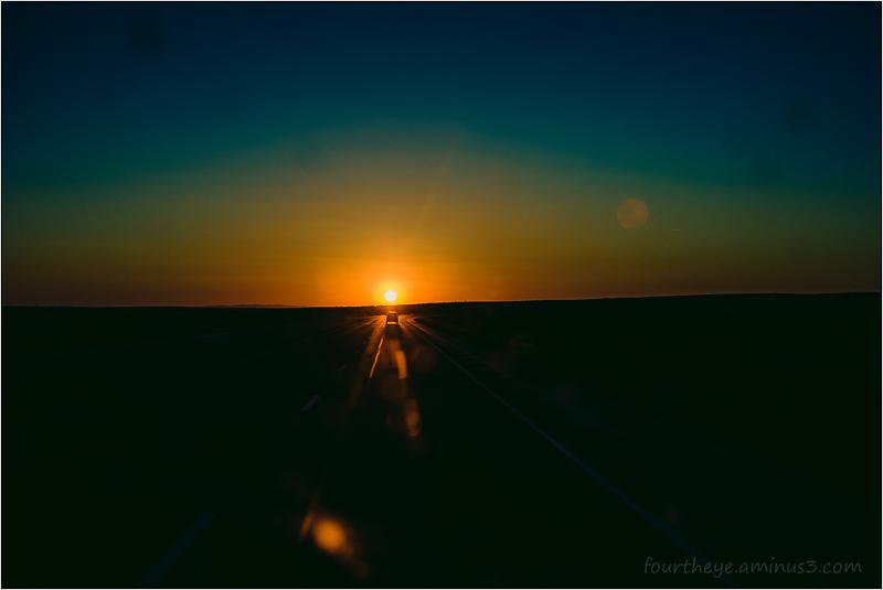 car driving into sun