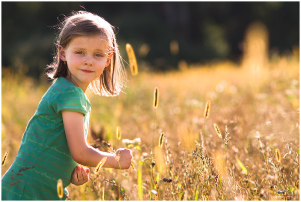 little girl walking through a field of wheat