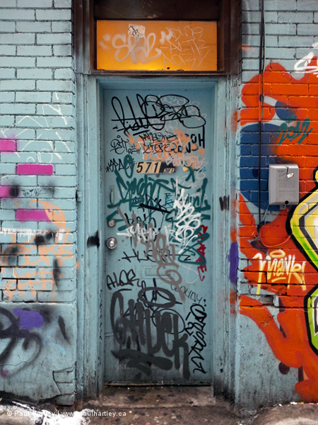 graffiti on a door in an alley