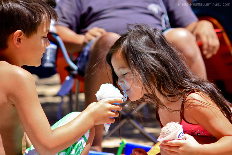Little kids sharing a snow cone