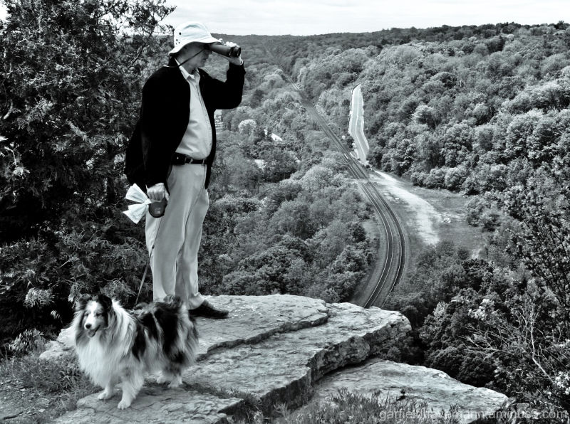 Man with dog standing on edge, with binoculars