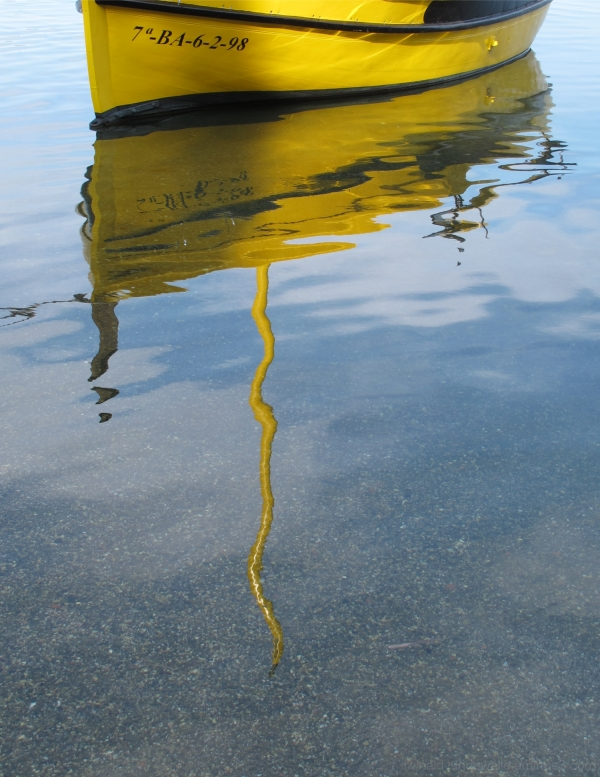 Reflection of a mast in calm water
