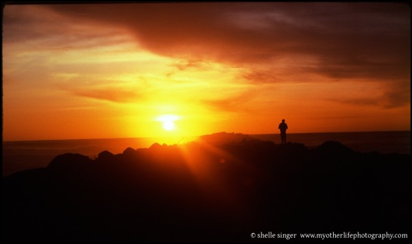silhouette of man on ocean rocks at sunset