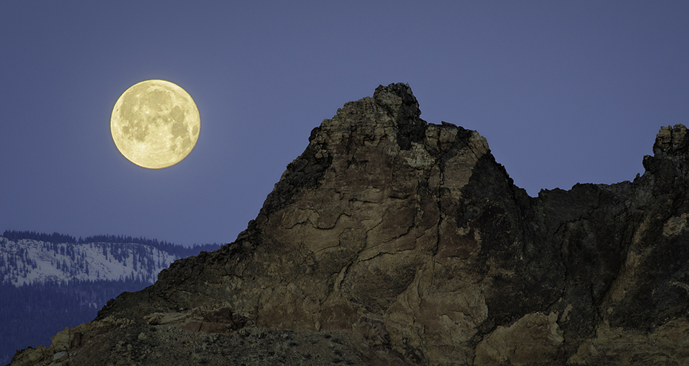 Moon setting over a volcanic dike in Capitol Reef