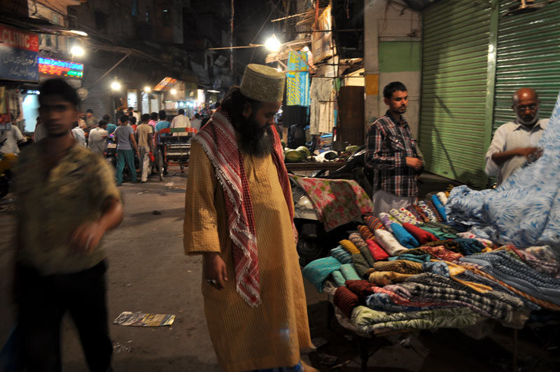 a man looking at materials  in the bazar old Delhi