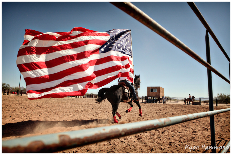 A woman on horseback ceremoniously begins a rodeo