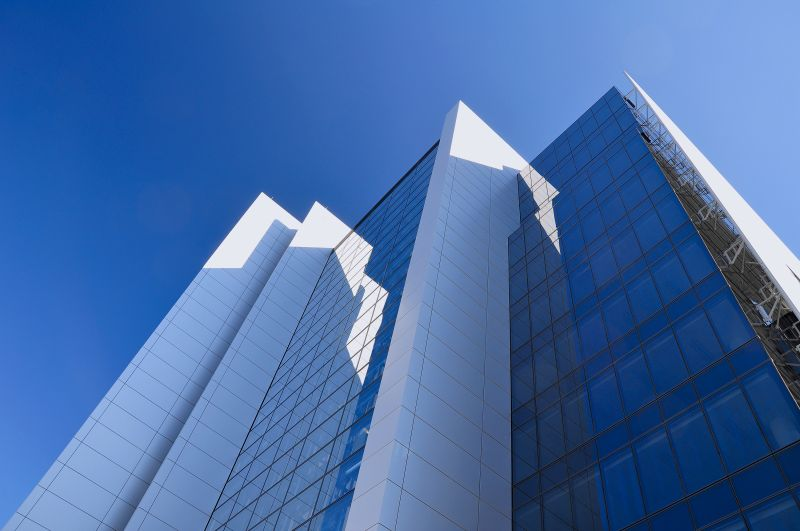 Office tower reflecting blue sky and white walls