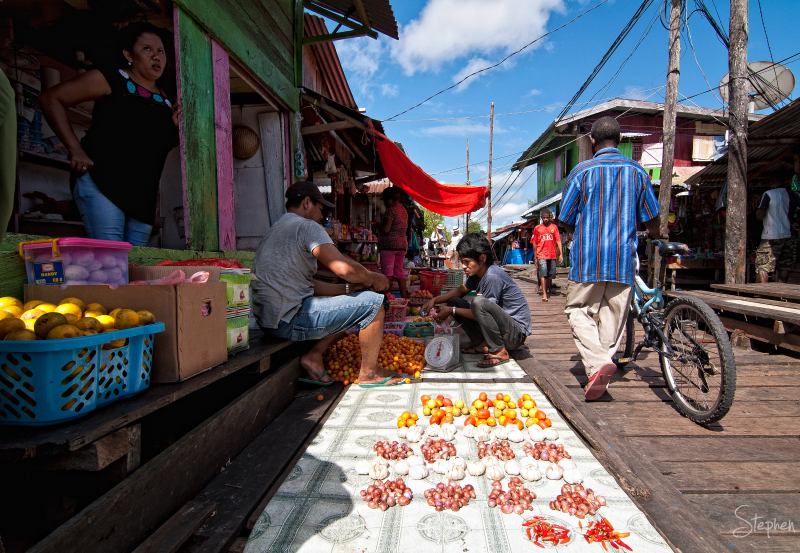 One of the markets on the boardwalk in Agats. The fresh fruit and vegetables you see here would be difficult to grow locally. Gardens need to be raised above the level of the mangrove swamp. As well as fruit and vegetables, other fresh food included fish and the red meat of the Cassowary (an Emu-like bird).