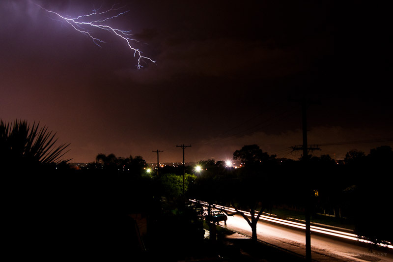 Lightning and a car racing down the street, trying