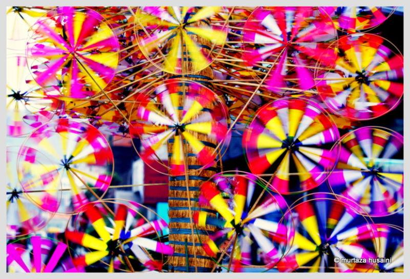 Street vendor selling paper made rainbow circles