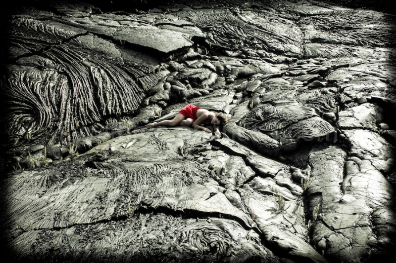 Girl, lost within a barren lava landscape.