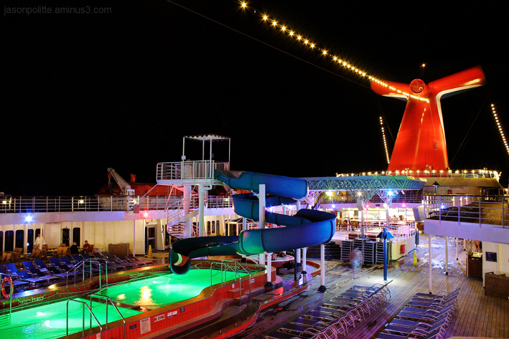 The Carnival Elation's Lido Deck lit up at night.