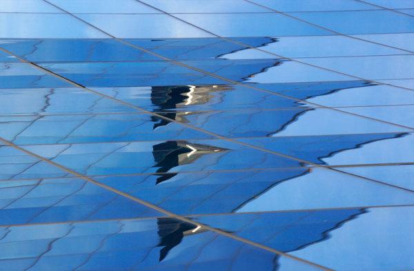 reflets nuages sur façade en verre