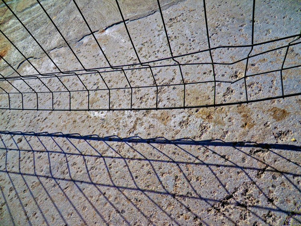 Un chemin de béton étroit entre deux grillages...