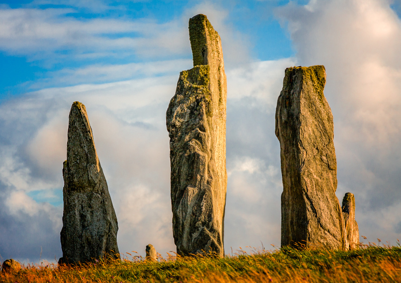 Three massive stones seem to stand guard at the Callanish Stones on the Isle of Lewis in The Outer Hebrides whilst basking in the late afternoon sun.