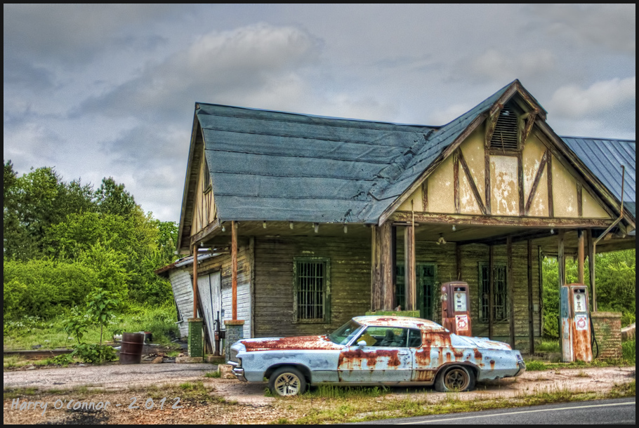 abandoned gas station with wrecked car