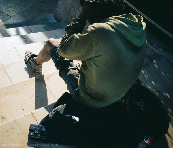 Homeless man sitting on steps.