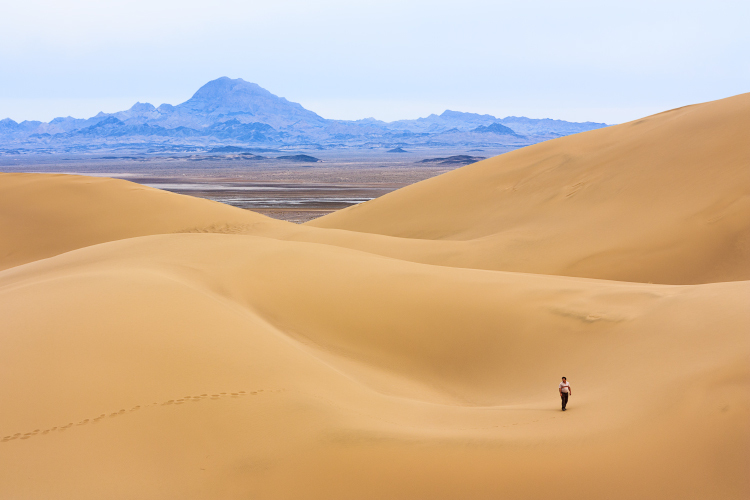 A man walking through the Maranjab desert ...