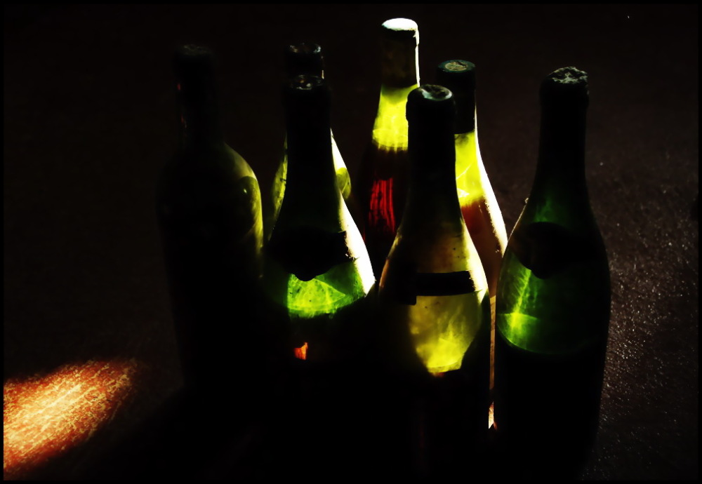 Old dusty wine bottles in a ray of light