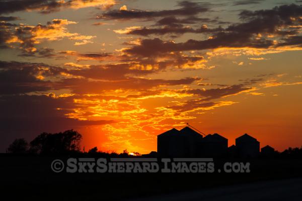 Harvest Sunset behind silhouette of grain bins.