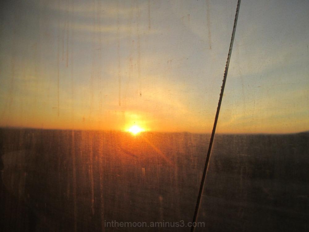 sunrise behind dirty broken window
