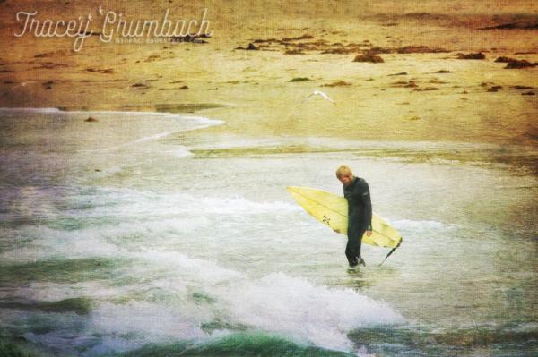 man walking with surfboard into ocean