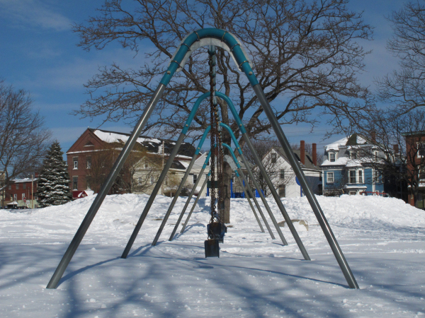 row of swings in snow with blue sky