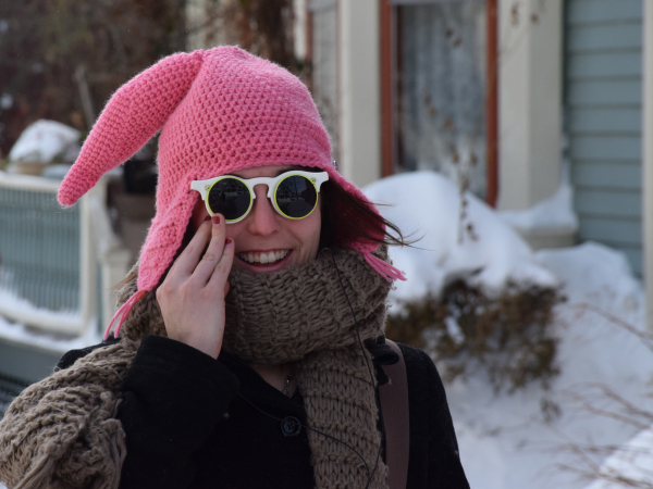 a woman walking in snowy street pink hat