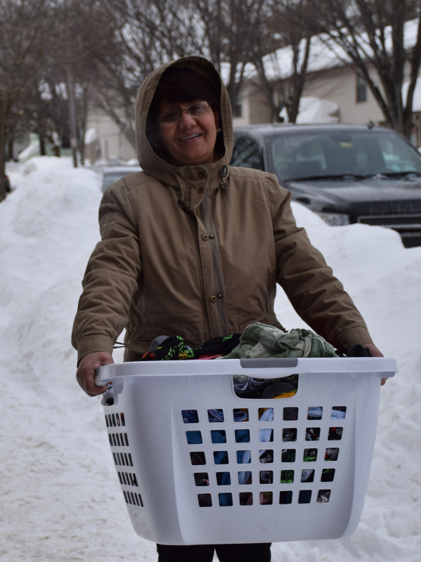 A woman carrying her laundry on snowy street