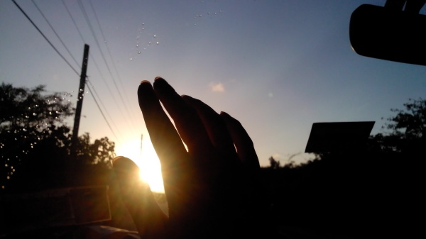 Hand covering the sunset from inside a car