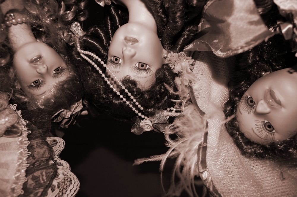 Three dolls looking down on the viewer