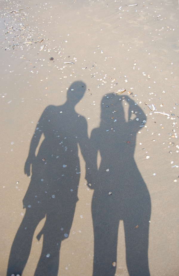 Shadows of a couple on the sand with seashells