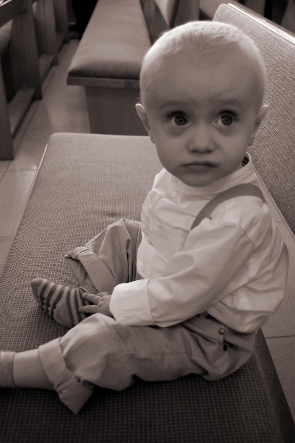 Baby boy sitting on a church bench