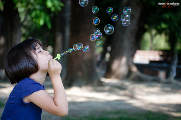 Young girl blowing bubbles outside in a park
