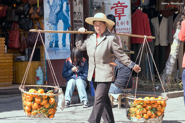 Chinese woman carrying oranges Dali Yunnan China